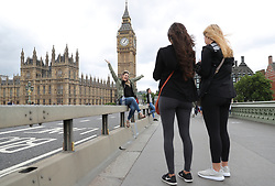 A woman poses for a photo on Westminster Bridge in London, next to barriers which have been placed there overnight following Saturday's terrorist attack.