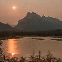 Shrouded in smoke from a forest fire, the sun rises over Vermillion Lakes and Mount Rundle in Banff National Park, Alberta, Canada.