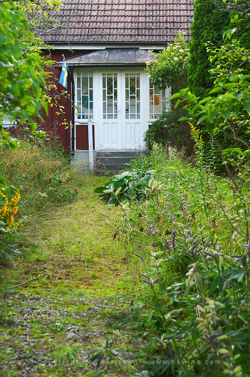 Traditional style Swedish wooden painted house. Overgrown unkempt garden. A veranda. Smaland region. Sweden, Europe.