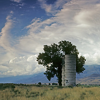A summer thunderstorm towers over abandoned silos in California's Owens Valley.