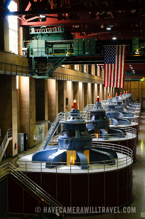 The tops of the 8 massive turbines on the Nevada side of the Hoover Dam (the Arizona side has another 9 turbines). These turbines generate electricity from the water flowing through the Hoover Dam and into the Colorado River below. The turbines stand about 30 feet tall from the ground in this room with another 40 feet below this level. The room is about 650 feet long. At top can be seen one of the massive cranes that can lift 300 tons.