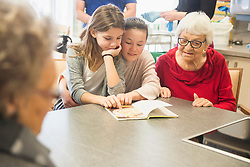 Senior women with girls reading book at rest home
