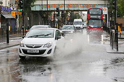 © Licensed to London News Pictures. 18/06/2020. London, UK. A car goes through a flood on Green Lanes, north London during heavy downpour. Photo credit: Dinendra Haria/LNP