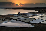 Janubio salt pan in South West Lanzarote is a tourist attraction but also produces a considerable amount of salt. The salt flats here produce more than 15,000 tons of salt a year, although that's only a third of the quantity produced 40 years ago.<br /> <br /> The method of salt extraction was introduced in 1895 and has changed little since last century. Large wooden staves known as palancas de madera, are employed, with sea water passing through narrow channels into ponds where the water simply condenses.<br /> <br /> The residue then passes through wooden ducts into salt pans where the process is completed, leaving bright sparkling crystals of salt.