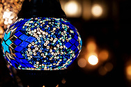 Colorful blue Moroccan lamp with blue glass mosaic design. Oriental style. Against bokeh background.