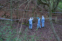 "© Licensed to London News Pictures. 07/12/2019. Gerrards Cross, UK. Forensic investigators hold up police cordon tape and look at a concrete pit indicated with an evidence identification marker as London's Metropolitan Police Service searches woodland in Gerrards Cross, Buckinghamshire. Police have been in the area conducting operations since Thursday 5th December 2019 and are searching two areas on Hedgerley Lane. In a press statement a Metropolitan Police spokesperson said ""Officers are currently in the Gerrards Cross area of Buckinghamshire as part of an ongoing investigation.<br /> ""We are not prepared to discuss further for operational reasons.""<br /> Photo credit: Peter Manning/LNP"