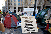 A sign berating the global elite and mass media.  The camp Occupy London Stock Exchange outside St Paul's Cathedral was in the morning served with eviction notice after months of legal battle with the Corporation of London. The site was occupied Oct 15th 2011.
