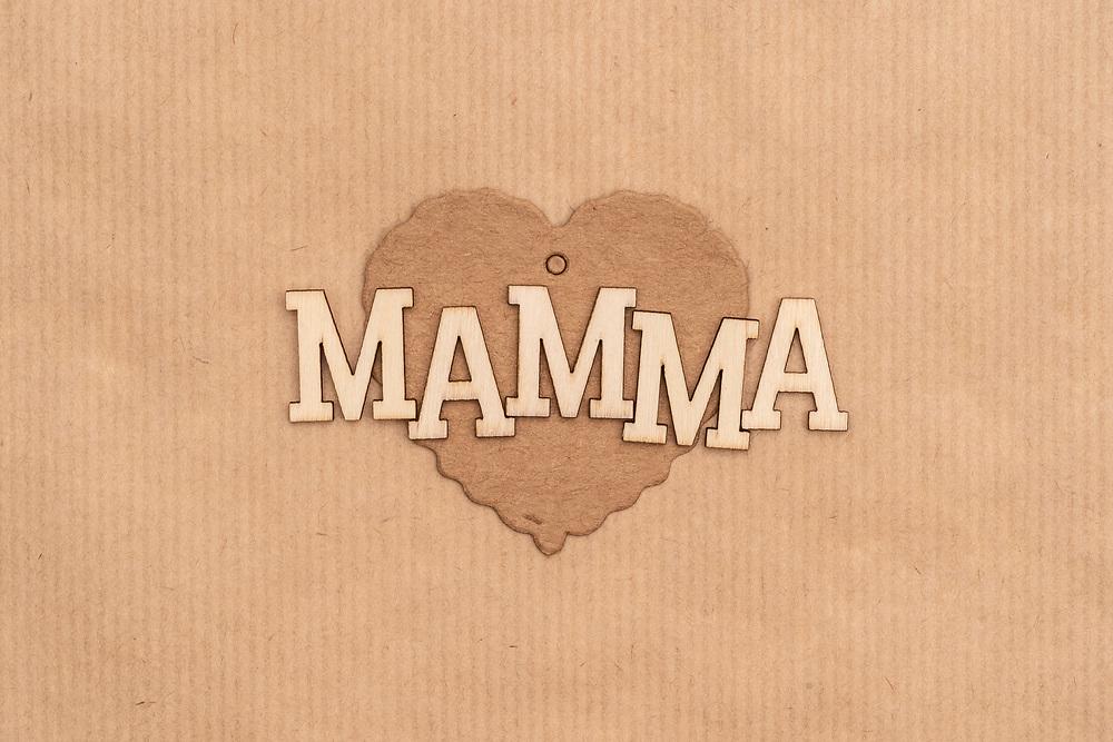 Trebokstaver med ordet «mamma» på et hjerte av grov kartong med bakgrunn av kraftpapir.