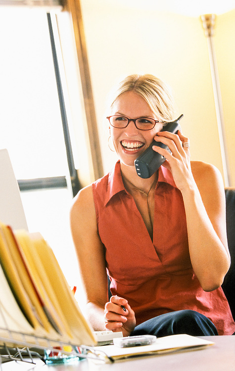 A young woman working in an office, talking on a cordeless telephone.