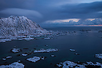 Steinstind mountain peak risies over village of Steine in winter, Vestvågøy, Lofoten Islands, Norway
