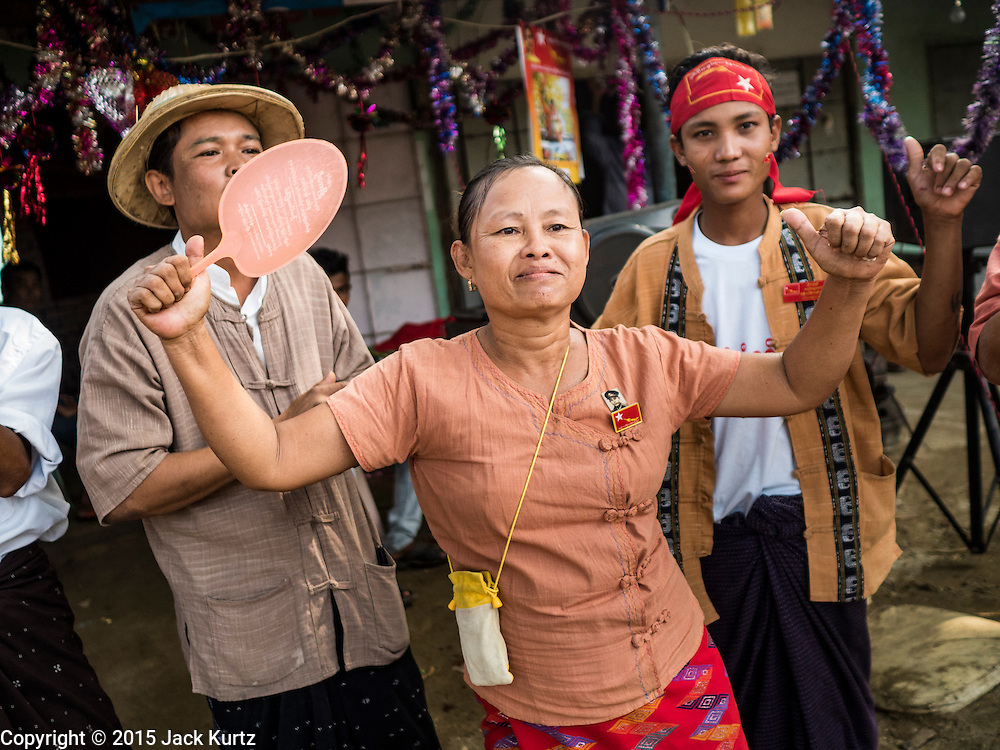 25 OCTOBER 2015 - SHWEPYITHAR, MYANMAR: NLD supporters in Shwepyithar, Myanmar, wait for a NLD motorcade to come to the small town about 90 minutes from Yangon. Political parties are in fill campaign mode in Myanmar (Burma). National elections are scheduled for Sunday Nov. 8. The two principal parties are the National League for Democracy (NLD), the party of democracy icon and Nobel Peace Prize winner Aung San Suu Kyi, and the ruling Union Solidarity and Development Party (USDP), led by incumbent President Thein Sein. There are more than 30 parties campaigning for national and local offices.     PHOTO BY JACK KURTZ