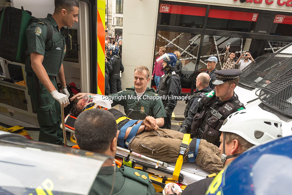 London Ambulance staff carry a protestor away on a stretcher following the occupation of a house on Beak St, Soho during the J11 protest in central London by the StopG8 anti-capitalist movement.  Tuesday 11  June  2013.  London, UK.<br /> Photo by: Mark Chappell/i-Images