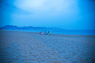 A young Vietnamese woman sits on a beach of Nha Trang at dusk, Vietnam, Southeast Asia