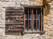 Barred window with old wood shutter in rock walled house at Passo Cibiana, Dolomites, Veneto, Italy, Europe.