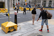 A man drops a used beer can in the street before walking on, near Bank underground station, outside the Bank of England, in the Square Mile, the capitals financial district, on 6th August 2020, in London, England.
