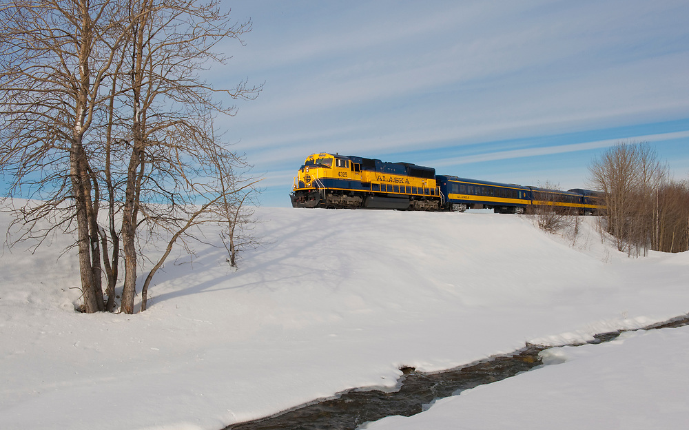 Alaska Railroad train passes open water on a clear day,