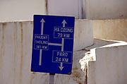 Blue roadside sign post to Phuent Sholing, Ha Dzong, Paro. Paro, Druk Yul, Bhutan. 12 November 2006