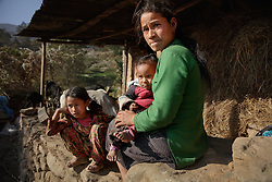 """Niruta, 24, with two of her children at the cow shed, where she spends most of her time. The family's struggles include multiple family sicknesses, including the baby's bout with severe diarrhea last year. """"She was very sick and we took her to the hospital in Kathmandu,"""" Niruta said. """"They gave some medicines and we spent about 1000 rupees but it didn't work. I didn't have money. She got better after we took her to the local shaman, who told us to sacrifice one black rooster. It was very difficult.""""<br /> <br /> Niruta and Durga were married 9 years ago, when they were just 14 and 16 years old in the Kagati village of Nepal. The 2015 earthquakes devastated Nepal and left girls and women in an increasingly vulnerable position, leading experts to believe child marriage rates will increase over the coming years."""