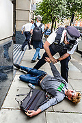 A police officer arrested a member of Extinction Rebellion activists group attempts to spray a message outside Department for Transport entrance, meanwhile other activists pelted red colour the building of Department for Transport's main entrance in Horseferry Road, and some others glued themselves outside DPT in central London on Friday, Sept 4, 2020. There are other Extinction Rebellion protests ongoing in London. Environmental nonviolent activists group Extinction Rebellion enters its 4th day of continuous ten days protests to disrupt political institutions throughout peaceful actions swarming central London into a standoff, demanding that central government obeys and delivers Climate Emergency bill. (VXP Photo/ Vudi Xhymshiti)