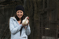 Portrait of a farmer woman with white chicken bird and smiling in farm, Bavaria, Germany