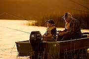 An elderly man and his grandson bond by fishing on a calm lake at sunrise