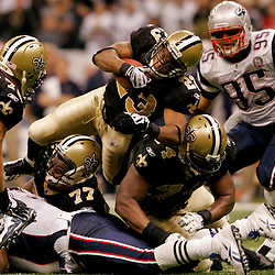 2009 November 30: New Orleans Saints running back Pierre Thomas (23) dives over the pile for extra yardage during a 38-17 win by the New Orleans Saints over the New England Patriots at the Louisiana Superdome in New Orleans, Louisiana.