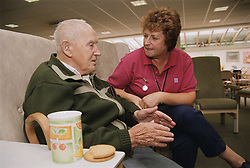 Elderly man sitting talking to female clinic assistant,