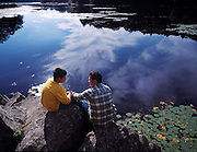 A father has a talk with his son while sitting on the edge of a beautiful pond
