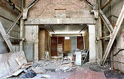 Derelict warehouse with broken furniture and boarded up entrance,