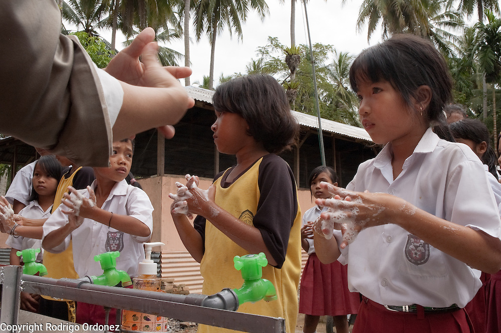 Lea, 10, (right) follows the instructions of one of her teachers as she washes her hands in the facilities provided by Save the Children in Elementary School 14 in Sungai Geringging.