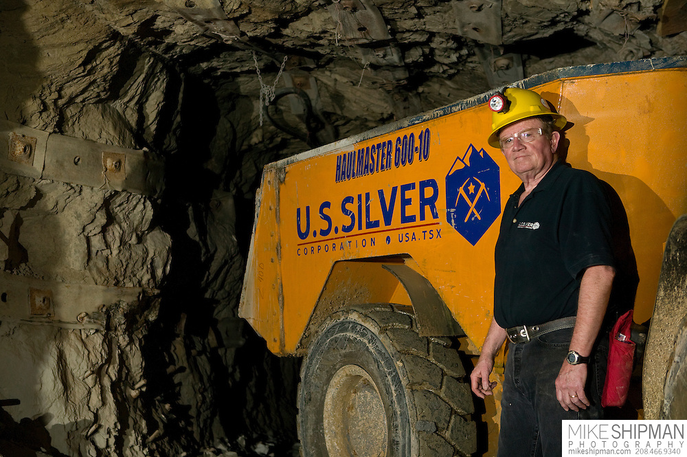 CEO stands next to a loader about 2300 ft underground in an Idaho silver mine