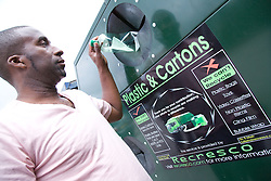 Man putting plastic bottle into a plastic and cartons recycling bank,