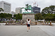 Chinese tourists take photos in front of a Statue of samurai, Kusunoki Masashige in the East Garden of the Imperial Palace, Tokyo Japan Friday July 22nd 2016