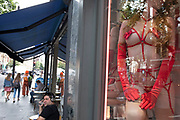 People continue their day passing a female mannequin red specialised underwear in the shop window of a Harmony adult store in London, United Kingdom.