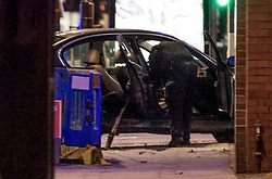 © Licensed to London News Pictures. 11/11/2020. London, UK. A police officer examines a car that crashed into Edmonton police station in north London. Videos of the incident show a man getting out from the car and setting light to a substance on the road before being detained by police. Photo credit: Marcin Nowak/LNP