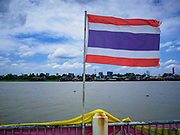 02 AUGUST 2018 - PAK KRET, NONTHABURI, THAILAND: A Thai flag along the Chao Phraya River on Ko Kret. Ko Kret (also spelled Koh Kret) is a small island in the Chao Phraya River in Nonthaburi province north of Bangkok. It is about 2 km long and 1 km wide. It has seven main villages, the largest and most populous being Ban Mon. Ko Kret was created in 1722 when a canal was dug in the Chao Phraya River to bypass a bend. Most of the people on the island are ethnically Mon, from the hills of western Thailand and eastern Myanmar (Burma). The island is popular as a weekend daytrip from Bangkok. The island is famous for the Mon style pottery made on the island.      PHOTO BY JACK KURTZ