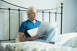 Mature man sitting in bed and reading newspaper