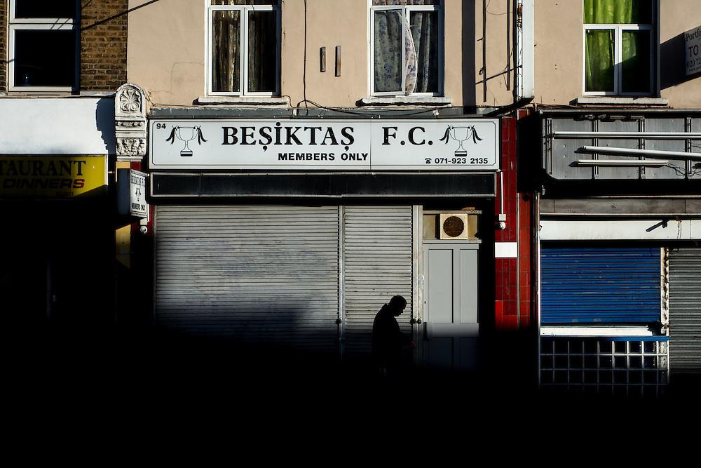 London, UK - 21 October 2014: A man walks past a closed Turkish Members club in Stoke Newington High Street at sunset