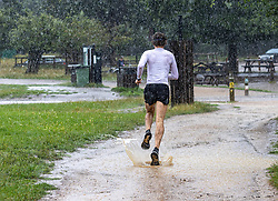 Licensed to London News Pictures. 07/08/202. London, UK. Summer washout. A runner gets caught in torrential rain in Richmond Park, southwest London today as thunderstorms continue to hit the South East with further showers expected tomorrow. Yellow weather warnings for England have been issued for thunderstorms with heavy rain, and possible flooding as the bad weather is set to continue until Monday. However brighter weather is finally forecast for next week with highs of 23c. Photo credit: Alex Lentati/LNP
