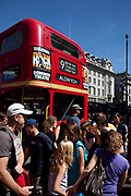 Crowds pass a red London Routemaster bus in the West End at Piccadilly. These iconic buses stipp operate on two herirage routes, and are much loved by tourists and locals alike.