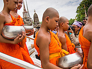 "22 JULY 2013 - PHRA PHUTTHABAT, THAILAND: Buddhist novices leave the Mondop (chapel that houses a footprint of the Buddha) during the Tak Bat Dok Mai at Wat Phra Phutthabat in Saraburi province of Thailand, Monday, July 22. Wat Phra Phutthabat is famous for the way it marks the beginning of Vassa, the three-month annual retreat observed by Theravada monks and nuns. The temple is highly revered in Thailand because it houses a footstep of the Buddha. On the first day of Vassa (or Buddhist Lent) people come to the temple to ""make merit"" and present the monks there with dancing lady ginger flowers, which only bloom in the weeks leading up Vassa. They also present monks with candles and wash their feet. During Vassa, monks and nuns remain inside monasteries and temple grounds, devoting their time to intensive meditation and study. Laypeople support the monastic sangha by bringing food, candles and other offerings to temples. Laypeople also often observe Vassa by giving up something, such as smoking or eating meat. For this reason, westerners sometimes call Vassa the ""Buddhist Lent.""     PHOTO BY JACK KURTZ"