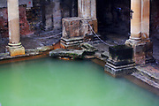 Roman baths at Bath, England. The Roman Baths complex is a site of historical interest in the English city of Bath. the Roman Bath House is supplied by water which bubbles up from the ground at Bath and fell as rain on the nearby Mendip Hills. The temple was constructed in 60-70 AD and the bathing complex was gradually built up over the next 300 years. During the Roman occupation of Britain, and possibly on the instructions of Emperor Claudius, engineers drove oak piles to provide a stable foundation into the mud and surrounded the spring with an irregular stone chamber lined with lead.