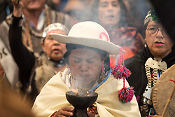 10 December 2019, Madrid, Spain: An indigenous woman blows incense, as a group of indigenous leaders set out to deliver a climate letter to the COP25 presidency, demanding that indigenous voices be heard in climate process at COP25 in Madrid.