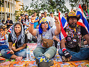 14 DECEMBER 2013 - BANGKOK, THAILAND: People listen to Suthep Thaugsuban, leader of the anti-government movement in Bangkok, during an anti-government rally in Bangkok. The Thai anti-government movement, called the People's Democratic Reform Committee (PRDC) sponsored a forum Saturday to establish guidelines for political reform in Thailand. The opposition leader, Suther Thaugsuban, said his movement will not participate in a similar forum, sponsored by the government scheduled for Sunday. Thailand's political impasse continues with the opposition calling for the caretaker government of Prime Minister Yingluck Shinawatra to step down. Yingluck has, so far, refused to step down from her caretaker roll. Crowds at the anti-government rallies have shrunk substantially since the collapse of the government earlier in the week.        PHOTO BY JACK KURTZ