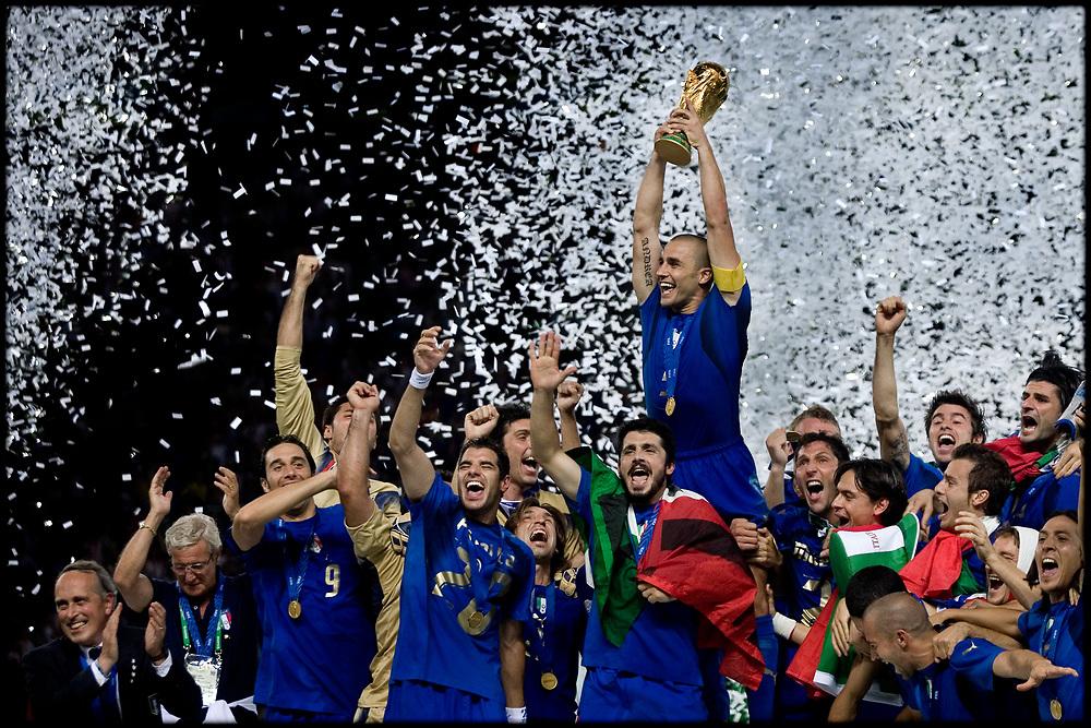 Duitsland. Berlijn, 09-07-2006<br /> WK Voetbal Finale: Italie-Frankrijk. <br /> Titelverdediger Frankrijk starte hoopvol tegen het altijd sterke Italie. Het had een mooi afscheid voor de franse voetballer moeten zijn maar Zinedine Zidane werd met een rode kaart van het veld werd gestuurd na het geven van een kopstoot aan Mazzarati. De fransen hielden lang stand maar na de verlenging en strafschoppen gingen de Italianen lachend met de Wereldbeker naar huis.  Italiaanse aanvoerder Fabio Cannavaro houdt de wereldbeker omhoog na de winst op medefinalist Frankrijk. <br /> Foto: Patrick Post / Sportstation