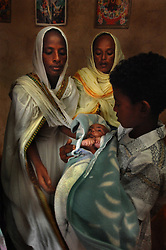 """Tiblits neighbor Zaid Tesheme, 31 has her baby baptized with the name Mihreteab inside Coptic St. Mary's chapel in the village of Fithi which means """"justice"""" on the outskirts of  Barentu, Eritrea August 27, 2006. During this ceremony, . The donkey that Tiblets received from the womens union """"Hamade"""", helped them prepare for the celebration afterwards.   (Photo by Ami Vitale)"""
