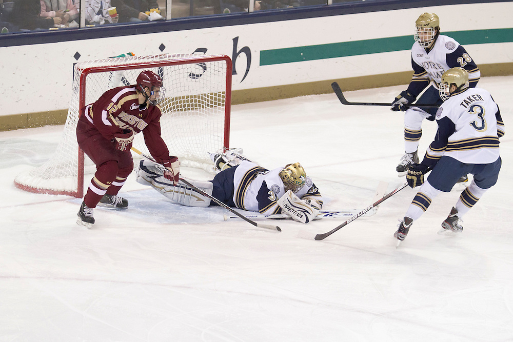 Notre Dame goaltender Mike Johnson (#32) makes save in action during NCAA hockey game between Notre Dame and Boston College.  The Notre Dame Fighting Irish defeated the Boston College Eagles 3-2 in game at the Compton Family Ice Arena in South Bend, Indiana.