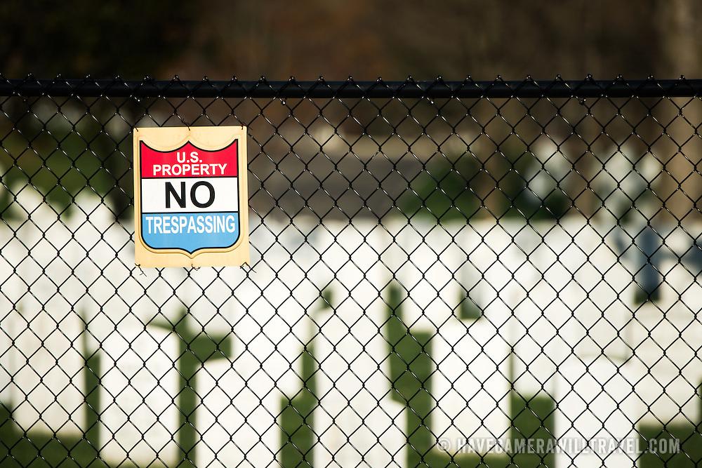 "A ""U.S. Property No Trespassing"" sign hangs on a fence around Arlington Cemetery."