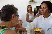 Priests conducting the ceremony giving communion. Often the lines between Candomble and Catholicism are blurred. This is especially true with the Sao Lazaro event in late January in Salvador, Bahia, Brazil, the city which is known as the home of Candomble. Sao Lazaro represents healing and the sick.