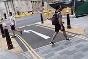 Pedestrians pass each other while walking through Bank in the City of London, the capital's financial district, on 6th August 2020, in London, England.